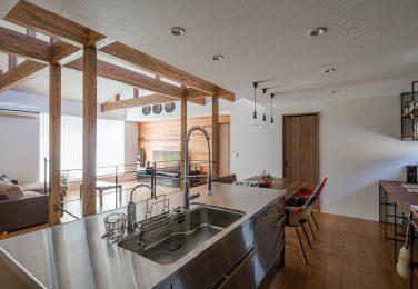 梁の見えるリビングを見渡せるステンレスのキッチン