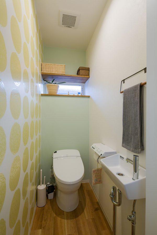 木目調の床にオレンジ水玉のクロスのトイレ
