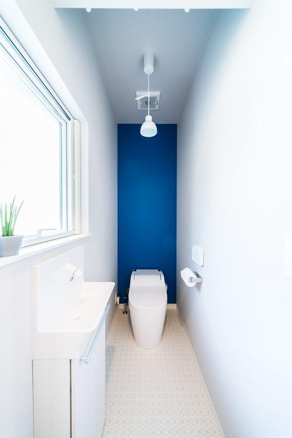白い壁にブルーのアクセントクロスのトイレ