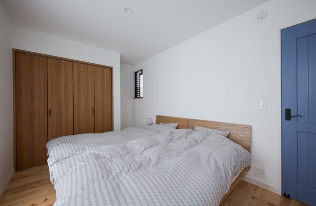 シンプルな室内にブルーの扉が映える寝室