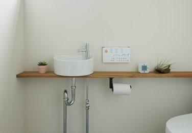 コンクリート調の床で造作棚のあるシンプルなトイレ
