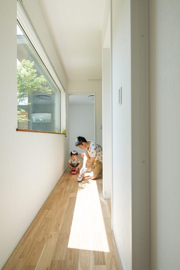 植栽の見える横長の窓から光が差し込む廊下