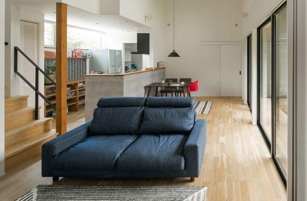 無垢の床に白い壁のシンプルな空間に大きな掃き出し窓があるリビング