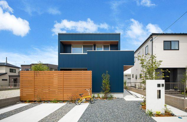 青のガルバリウムに板塀の木の色が映えるボックス型