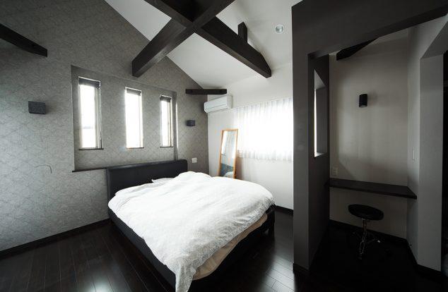 黒の化粧梁がアクセントのシンプルな寝室