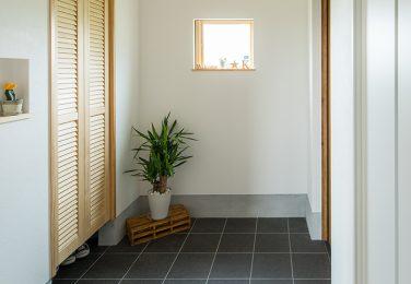 濃い色のタイルで正方形の小窓のある玄関