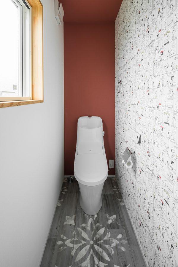 ステンシル柄の床にアメコミ風のクロスを組み合わせたトイレ