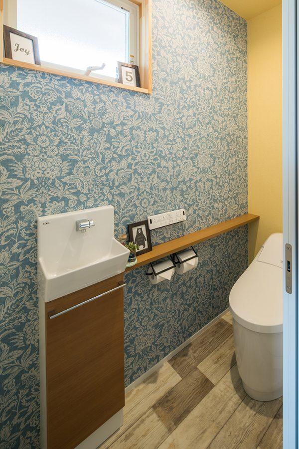 木目調の床に花柄のクロスを合わせたトイレ