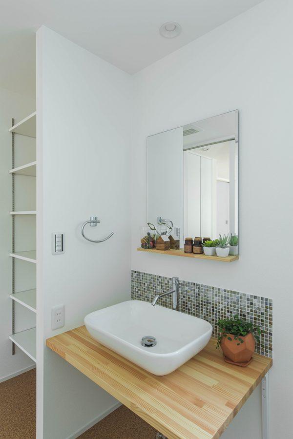 白壁にタイルと飾り棚が映える洗面所