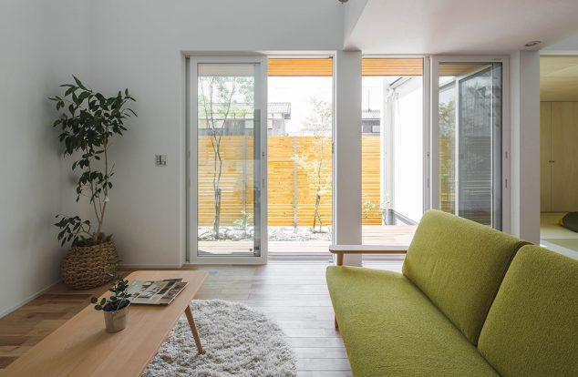 吹き抜けと掃き出し窓から光が入る、白壁のリビング