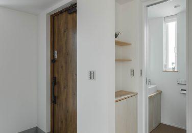洗い出し仕上げの土間に濃い木目の扉がある玄関