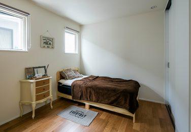 明るい木目調の床のある寝室