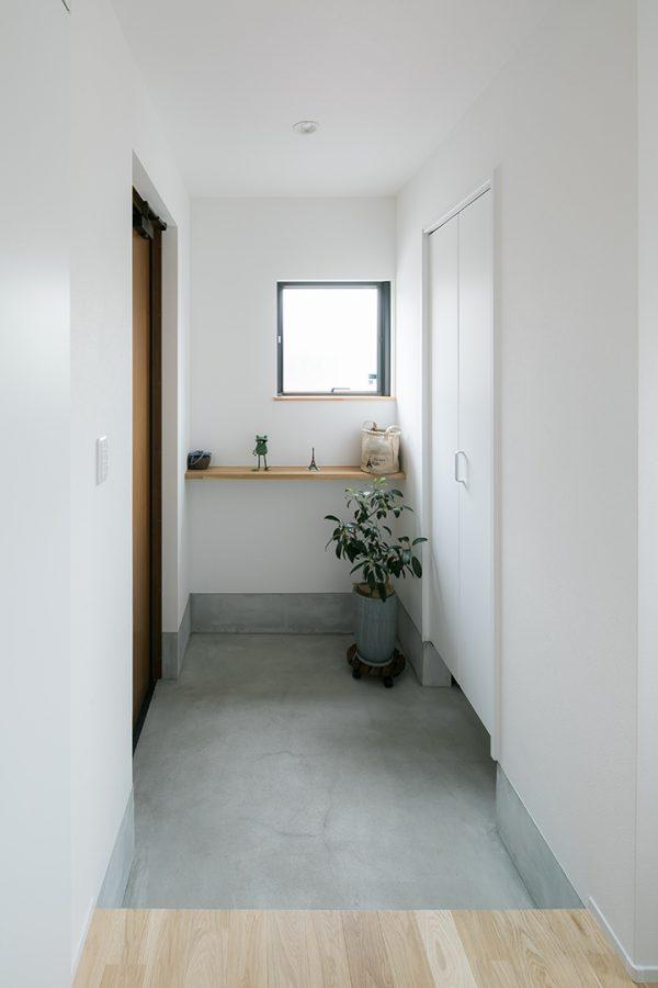 グレーと白で爽やな印象の、飾り棚のある玄関
