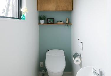 淡いブルーのアクセントクロスに収納と飾り棚のあるトイレ