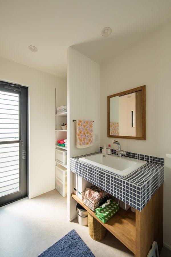 アクセントタイルと木の縁がかわいい洗面台