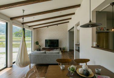 梁の見える勾配天井と窓によって開放感のあるリビング