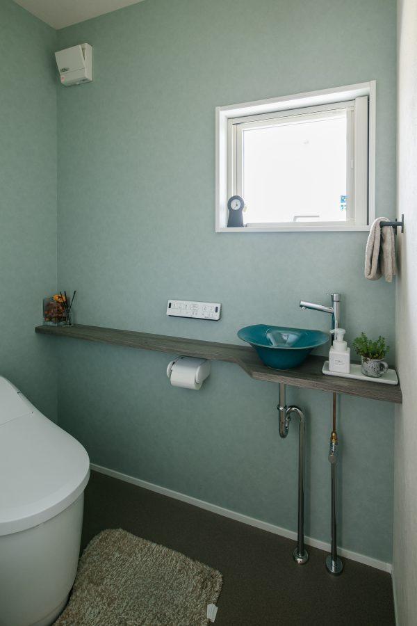 水色のクロスに青の手洗いボウルが映えるトイレ