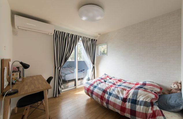 シンプルな室内にカーテンでアクセントを出した子供部屋