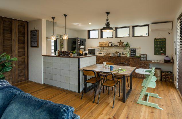 コンクリート調のキッチン腰壁にあわせた木とアイアンのダイニング