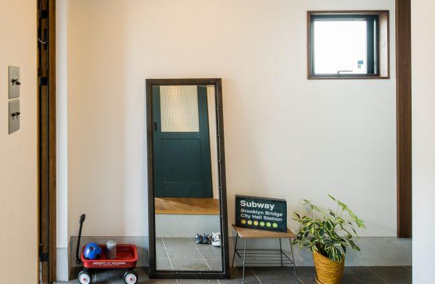 グレーのタイルに四角形の窓のあるシンプルな玄関
