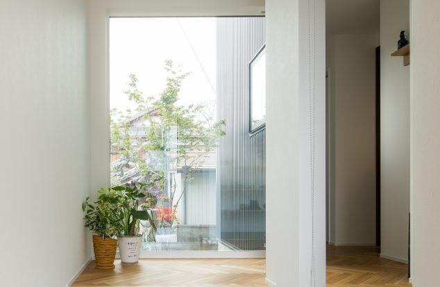植栽の見える大きな窓のある玄関