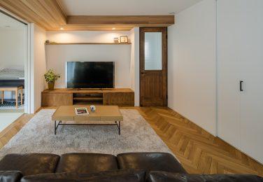 ヘリンボーンの床に暖かい木の色味のテレビボードと棚のあるリビング