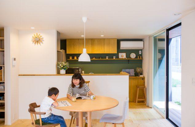 緑のアクセントクロスに明るい木目のキッチンの見えるカジュアルなダイニング