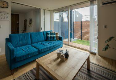 白で統一された室内にブルーのソファがアクセントのリビング