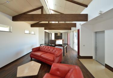 大胆な梁とソファーのコントラストで個性的なリビング