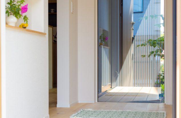 窓からのぞむ中庭と季節を感じるディスプレイのニッチに迎えられる玄関