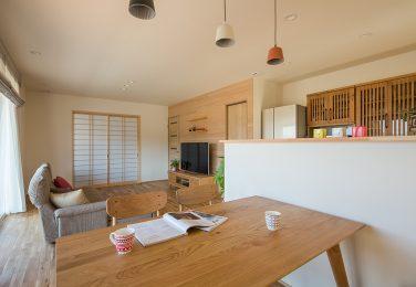 高めの腰壁でキッチンと区切られた、優しい木の色のダイニング
