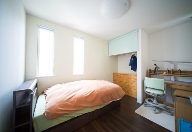 白い壁に縦長の窓が二つある寝室