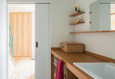 白壁にオーダーメイドの洗面台と飾り棚が映える洗面所