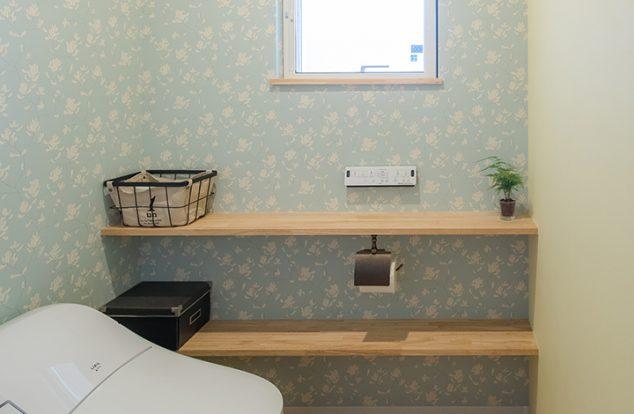 明るい木目調の床に水色のクロスを合わせたトイレ
