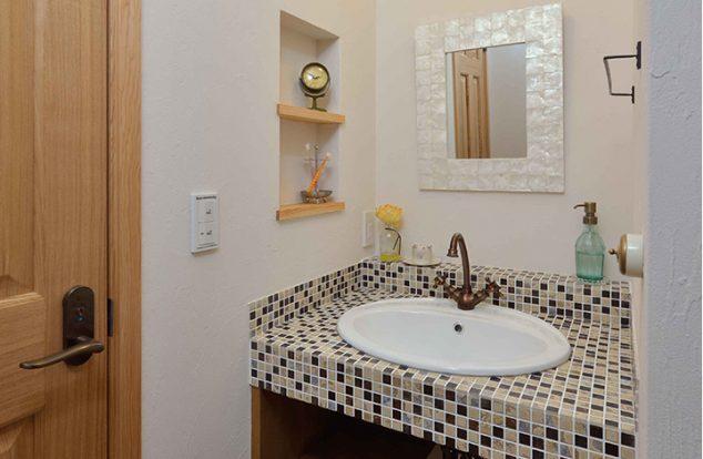 タイルの映える洗面台に飾り棚のあるかわいい洗面所