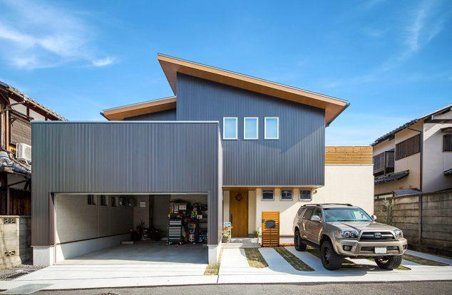 大きなビルドインガレージのある、ボックスと流れ屋根を合わせた外観