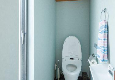 ネイビーのタイル調の床に造作棚のあるトイレ