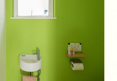 木目調の床にライトグリーンのクロスのトイレ