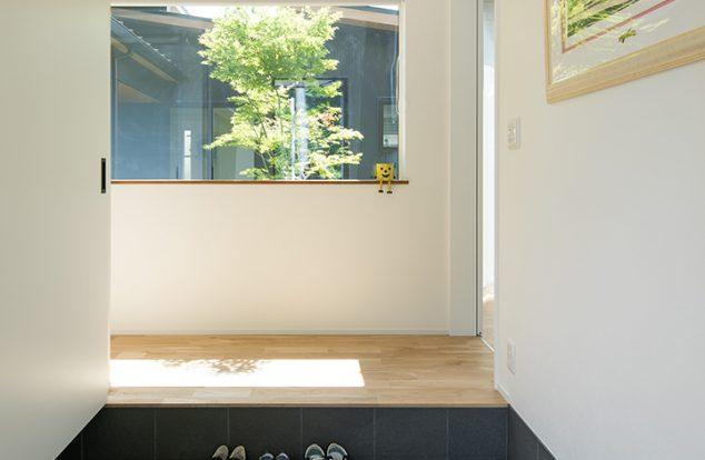 正面に植栽が見える大きな窓のある玄関