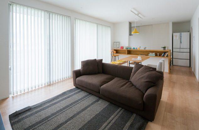 白色の室内に木の色のキッチンカウンターが映えるシンプルなリビング