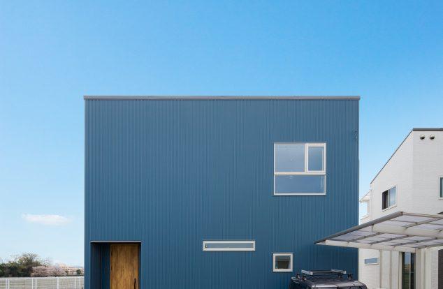 紺色ガルバリウムで窓を不規則に配置した箱型の外観