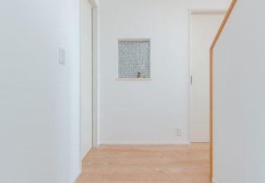 白ベースの色味で正面にニッチのある玄関