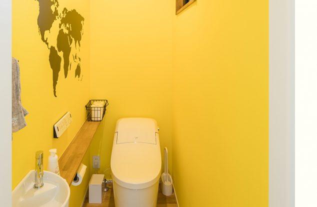 世界地図の入った黄色のクロスを使った、遊び心のあるトイレ