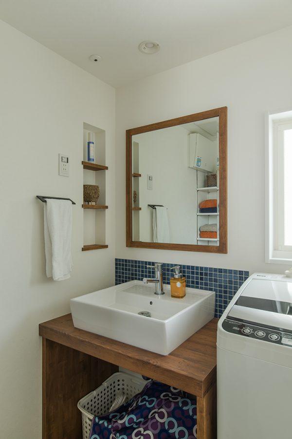 ブルーのタイルに飾り棚のある洗面所