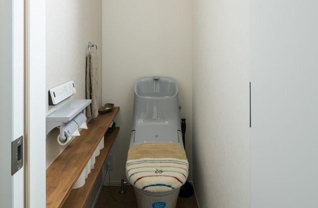 コルク風の床に造作棚のあるシンプルなトイレ