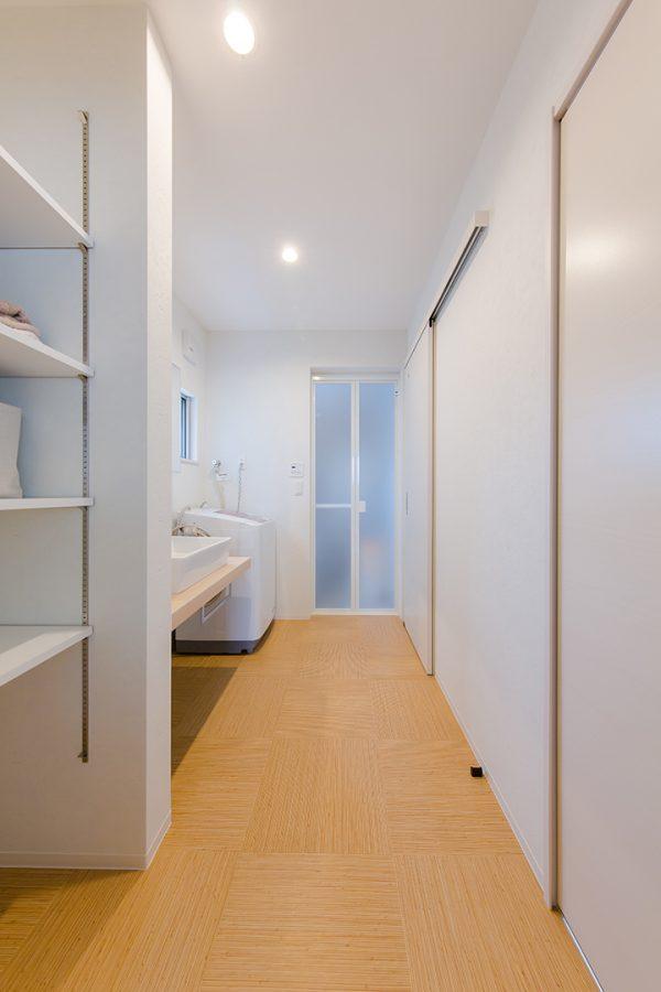木目調の床に白の収納棚の洗面所