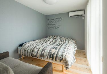 グレーで英字の入ったおしゃれなクロスの寝室
