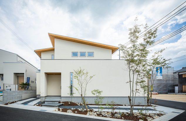 横長のボックス型に流れ屋根を組み合わせた白い外壁の外観