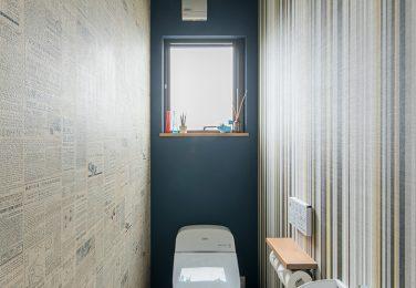 英字新聞とストライプ柄のクロスを使ったカッコいいトイレ