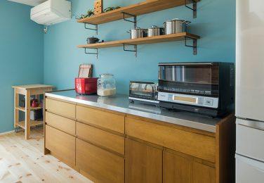 ブルーのアクセントクロスとオーダー食器棚のあるキッチン